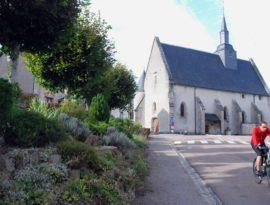 Un cycliste traverse le village, en arrière plan, l'église de Moux